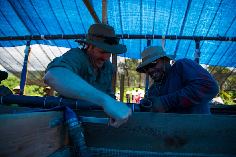 Two men work to manipulate a pipe that's attached to a wooden box while standing under a tarp in an outdoor work.