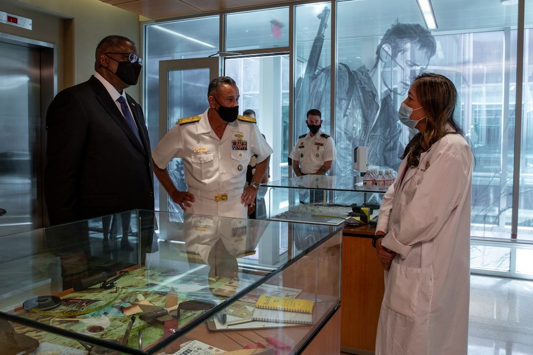 A man in a business suit and a man in a military uniform talk to a woman wearing a lab coat.
