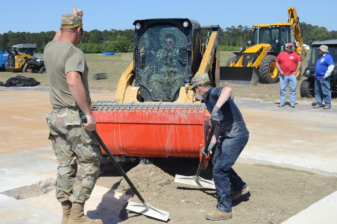 U.S. Air Force Master Sgt. Daniel Jennings and Senior Airman David Poynter, 169th Civil Engineer Squadron heavy equipment operators, place poured concrete into a repaired section of runway during an Expedient and Expeditionary Airfield Damage Repair (E-ADR) Joint Capability Technology Demonstration at McEntire Joint National Guard Base, South Carolina, April 22, 2021. The demonstration simulates the rapid repair of a battle damaged runway. (U.S. Air National Guard photo by Lt. Col. Jim St.Clair, 169th Fighter Wing Public Affairs)