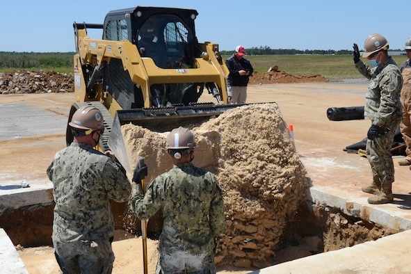 """U.S. Navy engineers from Navy Mobile Construction Battalion 133, Gulfport, Mississippi, fill in an excavated hole during an Expedient and Expeditionary Airfield Damage Repair (E-ADR) Joint Capability Technology Demonstration at McEntire Joint National Guard Base, South Carolina, April 22, 2021. The demonstration field tests the """"just enough, just-in-time"""" repair capability on a decommissioned runway at McEntire Joint National Guard Base. The Department of Defense's E-ADR concept uses local materials and minimal personnel and equipment in order to expedite a temporary runway repair. (U.S. Air National Guard photo by Lt. Col. Jim St.Clair, 169th Fighter Wing Public Affairs)"""