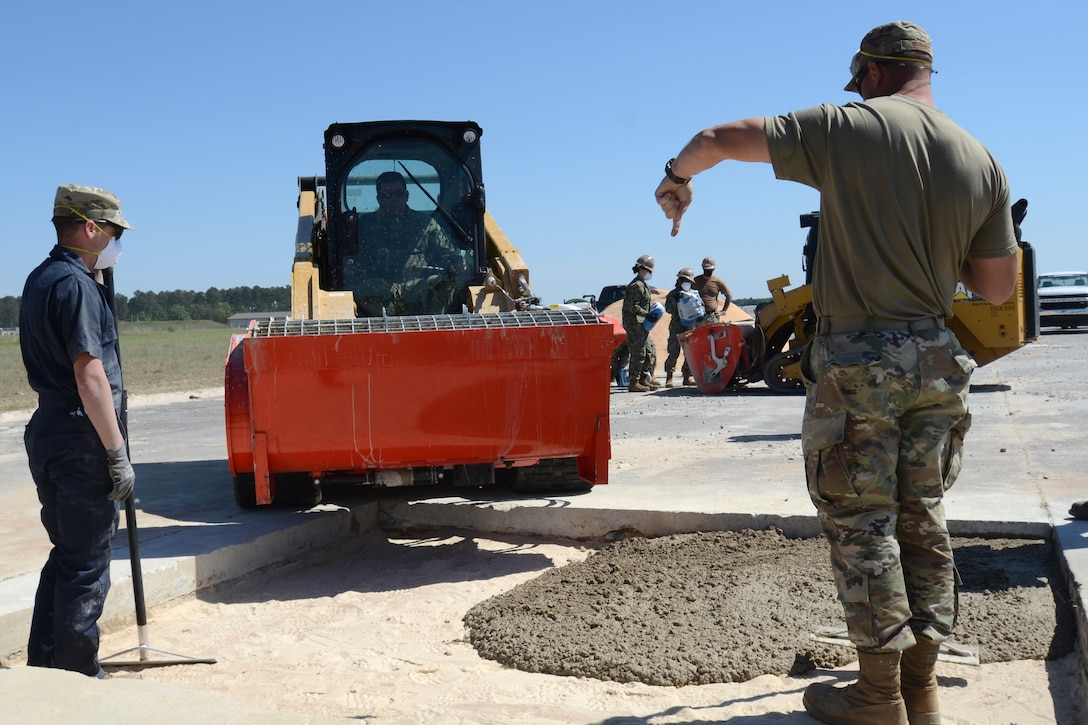 U.S. Air Force Master Sgt. Daniel Jennings (right) and Senior Airman David Poynter, 169th Civil Engineer Squadron heavy equipment operators, place poured concrete into a repaired section of runway during an Expedient and Expeditionary Airfield Damage Repair (E-ADR) Joint Capability Technology Demonstration at McEntire Joint National Guard Base, South Carolina, April 22, 2021. The demonstration simulates the rapid repair of a battle damaged runway. (U.S. Air National Guard photo by Lt. Col. Jim St.Clair, 169th Fighter Wing Public Affairs)