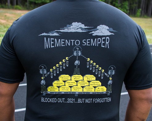 """Master Sgt. Ronald Murphy II showcases his shirt that commemorates the 12 fallen team members with the slogan """"Memento Semper,"""" which translates to """"Remember Always."""" Airmen from Dobbins came together for a Port Dawgs Memorial Run that was held at the base track on May 2. (U.S. Air Force photo/Staff Sgt. Josh Kincaid)"""