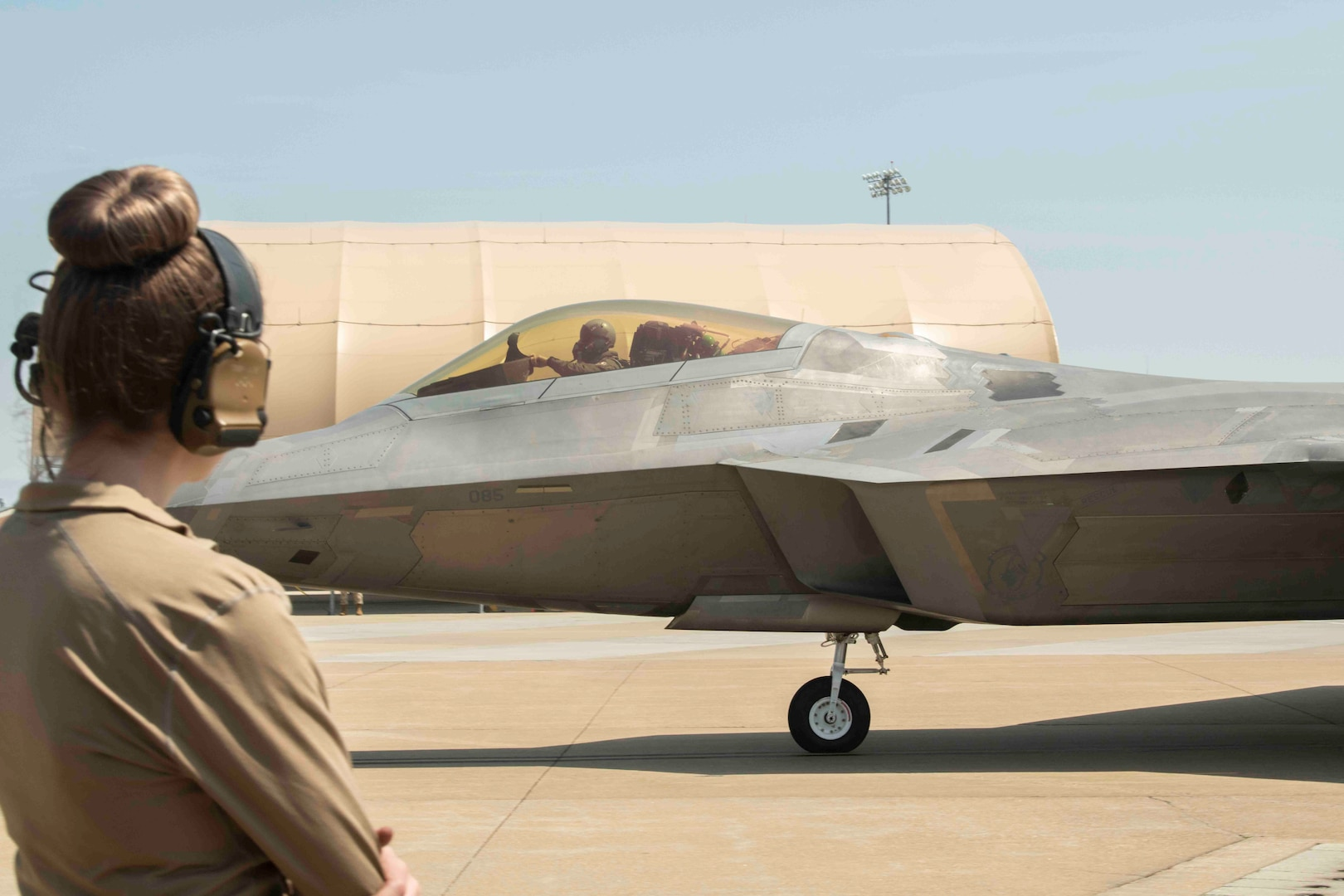 An airman looks on as F-22 tail #85 taxies towards its first flight in more than a year