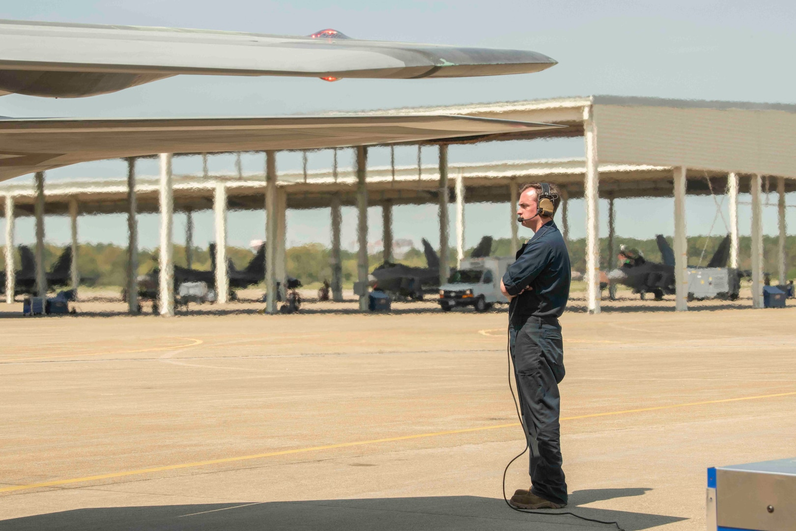 A crew chief looks on as an F-22 Raptor prepares to take flight