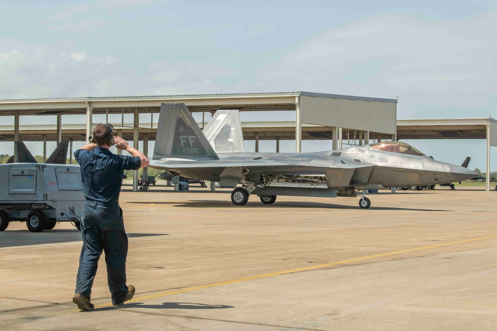 An F-22 crew chief waves the jet back in after its first flight in over one year