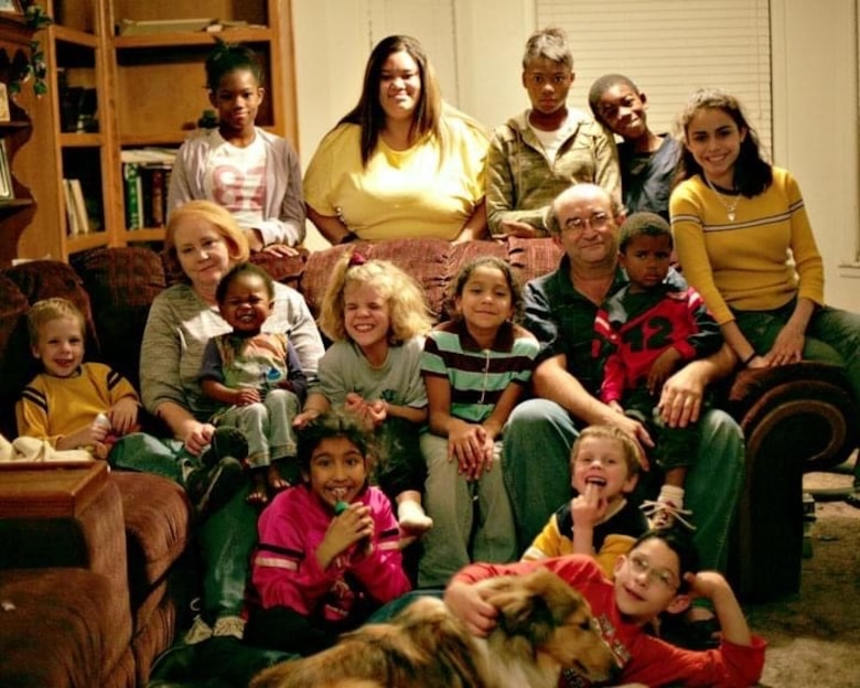 Airman 1st Class Jessica Makenna Martinez Greenlee, 36th Force Support Squadron services journeyman, bottom left, poses for a photo with her parents, Lonny and Donna Greenlee and 12 of her 20 other siblings from the Greenlee home in Wolfforth, Texas, November 24, 2005. Greenlee was placed in foster care at the age of three with three of her siblings. After being in a few homes, a couple from Lubbock, Texas showed interest in adopting all four of them, giving them the chance to grow up together with the company of 19 other children they had and adopted. (Courtesy photo)