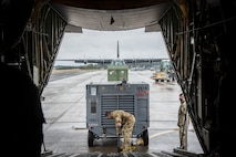 A U.S. Air Force Airman loads cargo onto a C-130J Super Hercules from the 374th Airlift Wing during the Beverly Sunrise 21-05 Readiness Exercise at Misawa Air Base, Japan, May 2, 2021. The C-130s are transporting cargo and personnel to support the 35th Fighter Wing's Agile Combat Employment capabilities. (U.S. Air Force photo by Airman 1st Class China M. Shock)