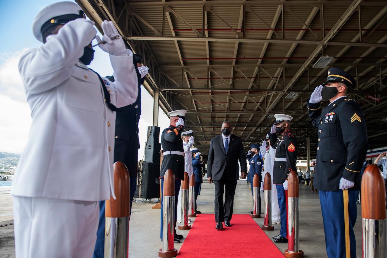 Defense Secretary Lloyd J. Austin III walks between two rows of service members.