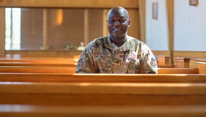 Chaplain (Maj.) Bitrus Cobongs, head chaplain for the 403rd Wing at Keesler Air Force Base, Miss., sits on a pew in Keesler's Triangle Chapel April 11, 2021. Cobongs's life began over 6,000 miles away in Nigeria where his early aspirations consisted of being a youth minister, but through closed and opened doors, he ended up serving in the U.S. military. (U.S. Air Force photo by Staff Sgt. Kristen Pittman)