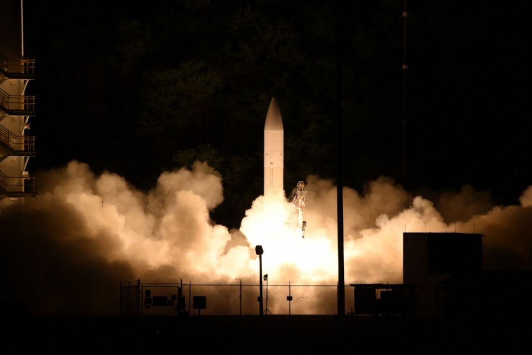A missile launches at night in a cloud of fire and smoke.