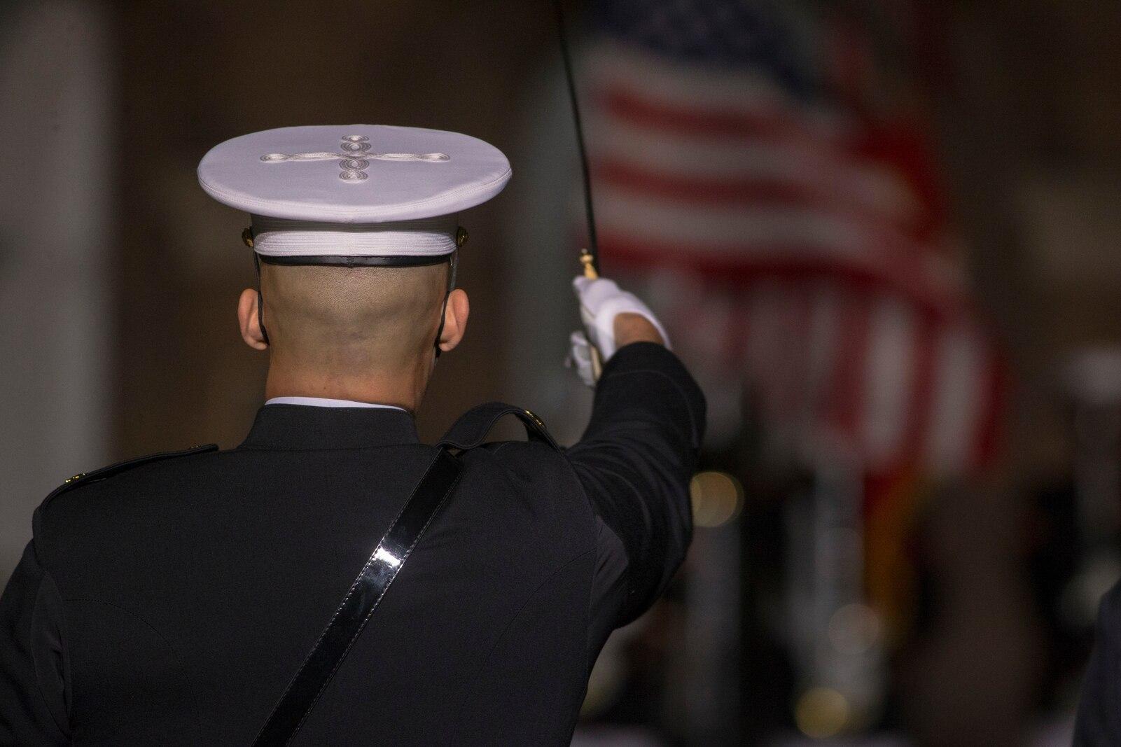 "Major Alec Pourteau, parade commander, executes ""draw sword"" during the Friday Evening Parade at Marine Barracks Washington, D.C., April 30, 2021."