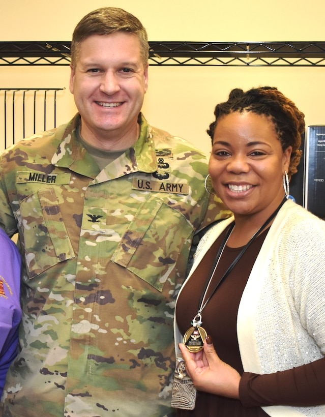 """IN THE PHOTO, Memphis District Commander Col. Zachary Miller (left) coins Procurement Analyst TiJuana' TJ' Harris in January of 2020 for going above and beyond in her work. Harris was recently provided the chance to apply for a 120-day developmental assignment at the division level, where she said she would learn even more about the """"Whys"""" of USACE contracting."""