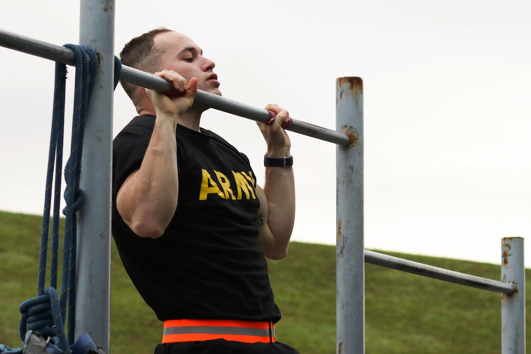 A soldier does a pullup.