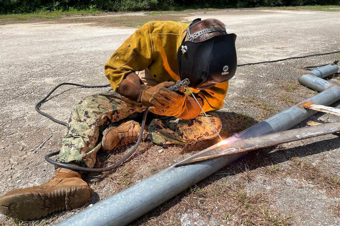 A sailors welds a metal pipe as sparks fly.