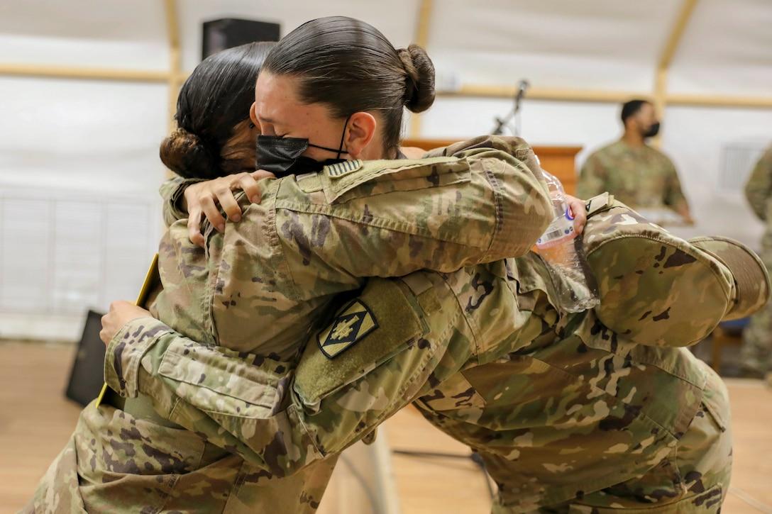 Two service members hug.