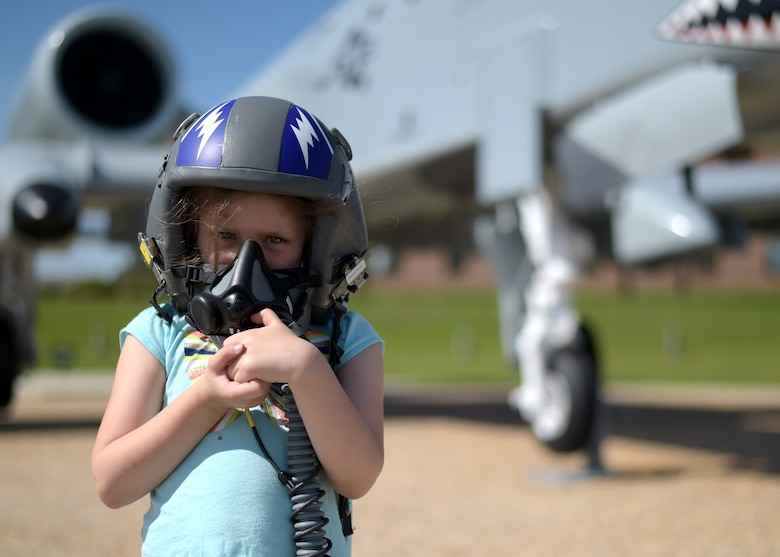 Girl in helmet in front of A-10 attack aircraft