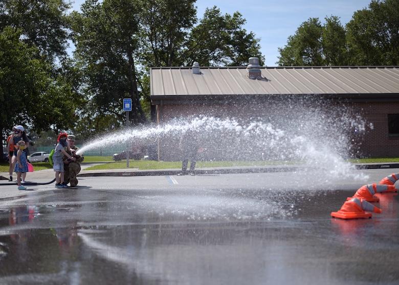 Airman shooting a fire hose