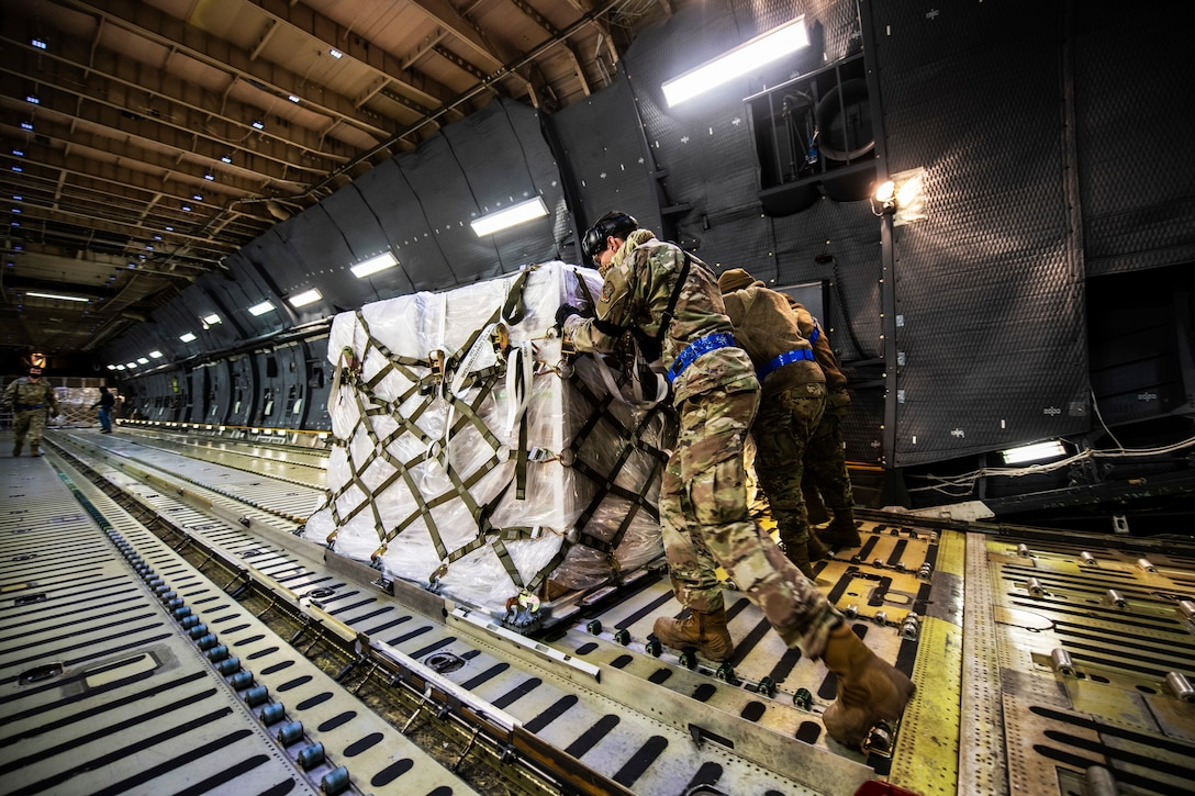 Several airmen wearing face masks and gloves push pallets of COVID-19 supplies to assist India.