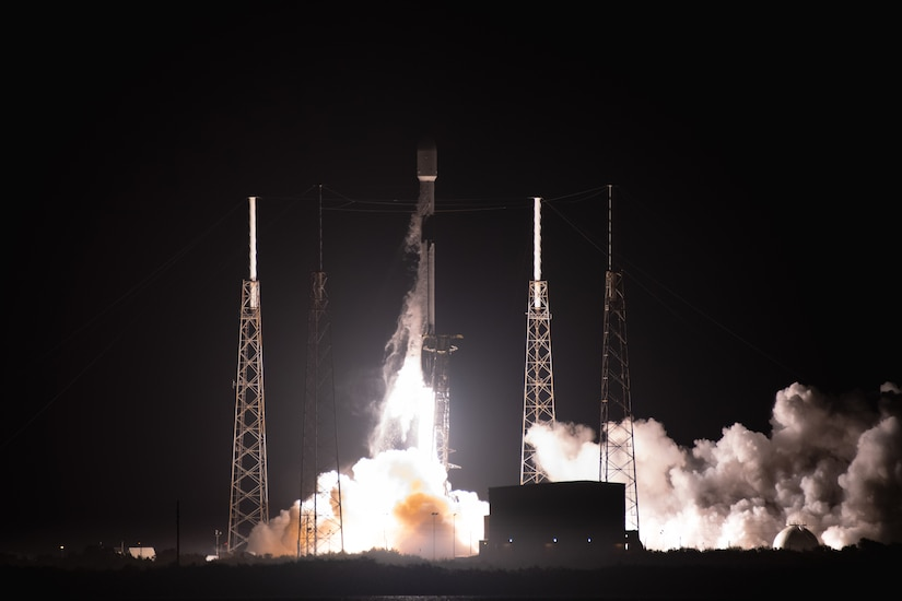 Smoke billows against the night sky as a rocket takes off.