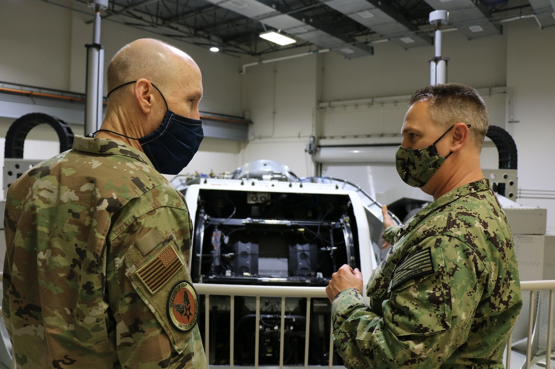 Navy Capt. Richard Folga, Department Head, Engineering and Technical Services and Program Manager of the Kraken, Naval Aerospace Medical Research Laboratory, NAMRU-Dayton and Gen. David Allvin stand on a balcony in front of the Disorientation Research Device, also known as the Kraken. The device is a one of a kind national scientific asset that provides a platform for basic science and applied research through simulation of aviation environments with customizable capsule configurations supporting one or two side by side occupants. (U.S. Navy photo/Megan Mudersbach)
