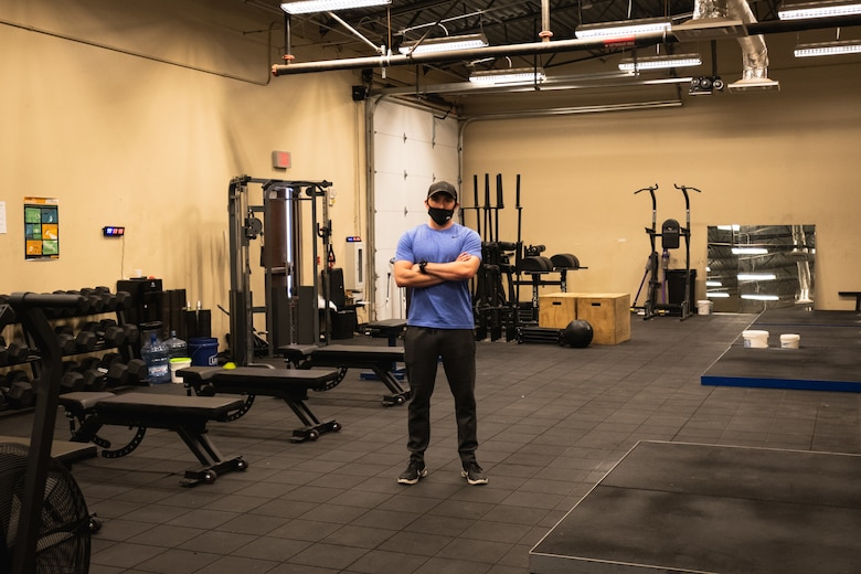 Man in a purple shirt, black pants, black hat and black mask stands in a large, dimly lit room surrounded by gym equipment.