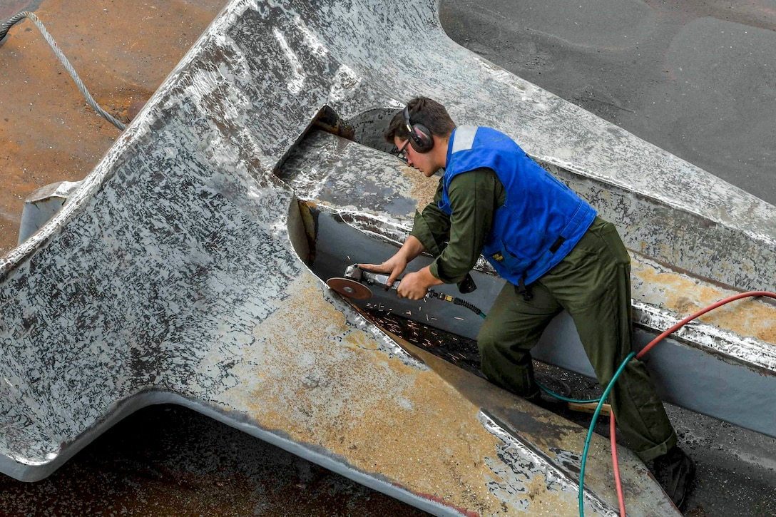 A sailor uses a tool on a large anchor.