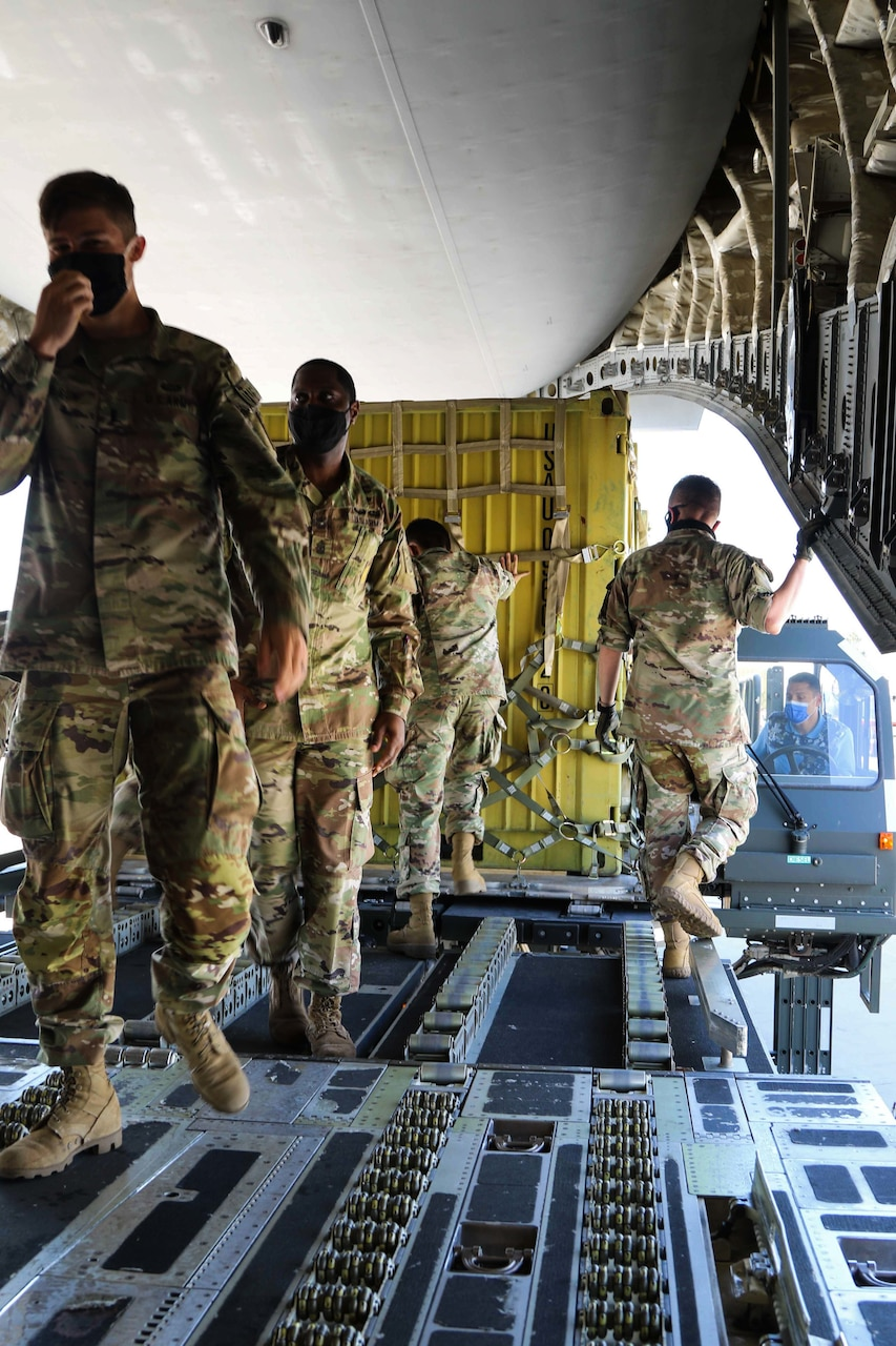 Service members in military uniforms stand inside an aircraft.