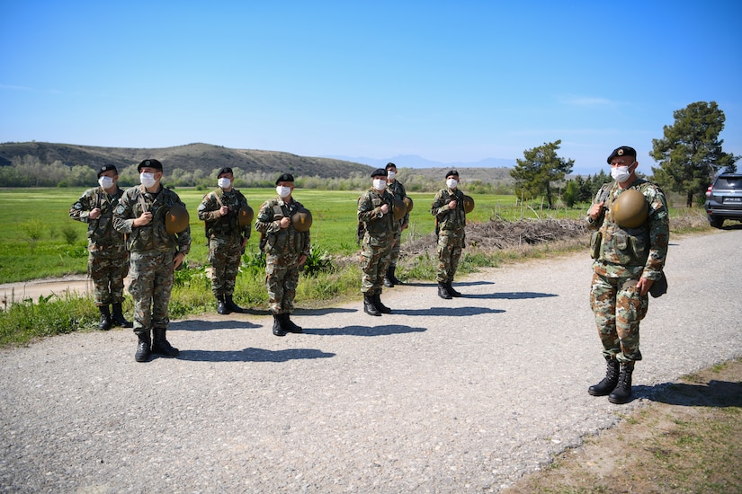 Eight men in military uniforms stand in formation on a gravel road. In the background are mountains.