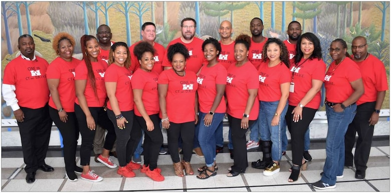 """IN THE PHOTO, Memphis District Procurement Analyst TiJuana' TJ' Harris (fourth from the left, front row) poses for a group photo with her Contracting 'family' after their Fiscal 'New Year Party"""" in September of 2019. Harris was recently provided the chance to apply for a 120-day developmental assignment at the division level, where she said she would learn even more about the """"Whys"""" of USACE contracting."""