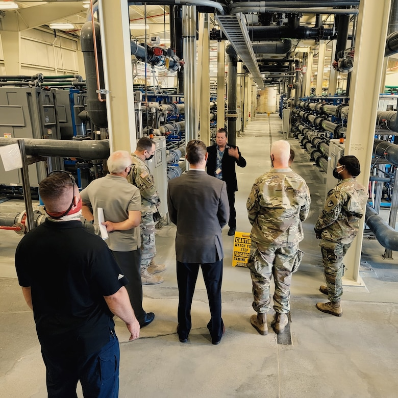 Christopher Woodruff, water resources manager, Fort Irwin Department of Public Works, background center, briefs U.S. Army Corps of Engineers Deputy Commanding General for Military and International Operations Maj. Gen. Jeffrey L. Milhorn and U.S. Army Corps of Engineers South Pacific Division Commander Brig. Gen. Paul Owen about the Fort Irwin Water Works Water Treatment Plant during an April 26 tour of the facility at Fort Irwin, California.