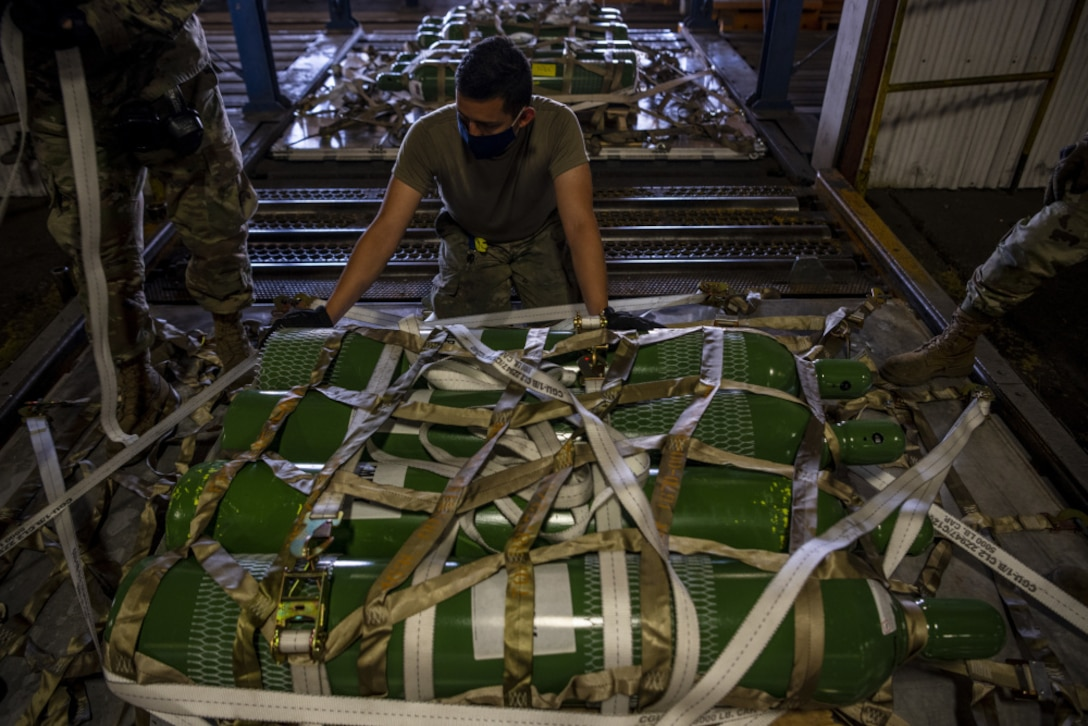 A military member grasps cargo netting over a pallet of green cylinders.