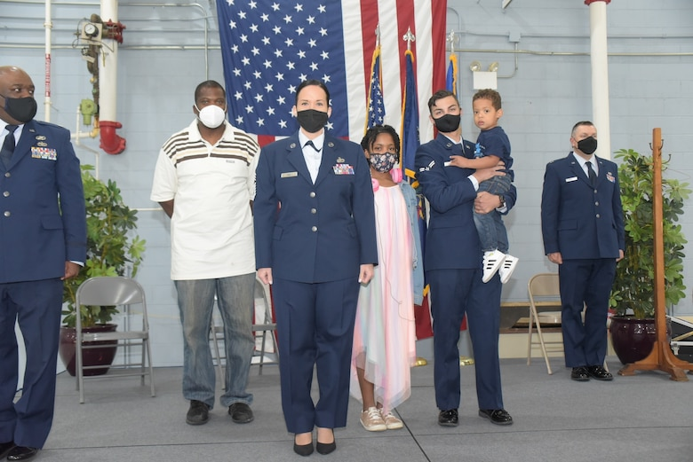 A female chief master sergeant in dress blue uniform poses with her family during her promotion ceremony.