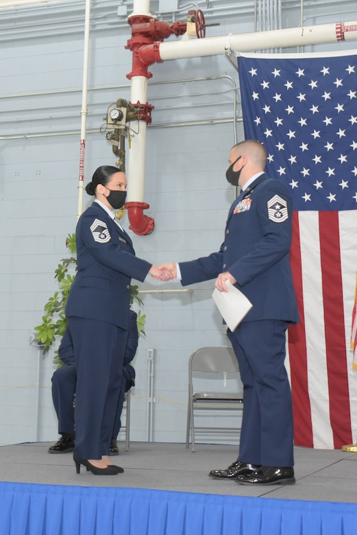 A female chief master sergeant in Air Force dress blue uniform shakes hands with a male chief master sergeant.
