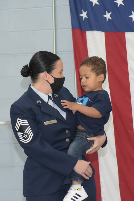 A women in Air Force Dress blues holds her toddler son.
