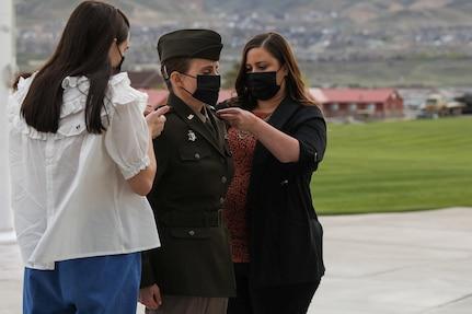 Women pin rank on shoulders of soldier