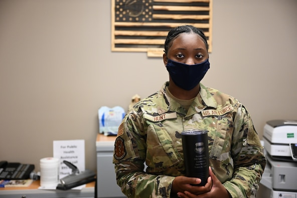 Airman 1st Class Shadrica Hunt poses with weasel mug.