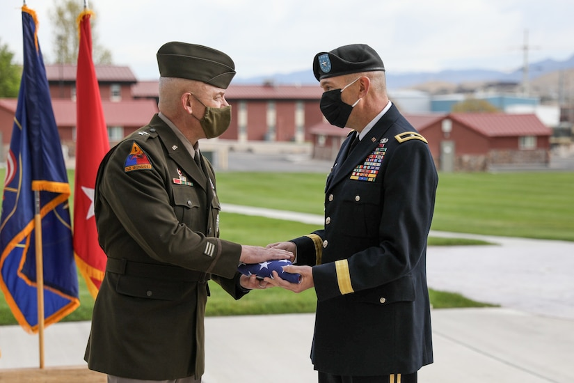 A soldier hands a flag to another soldier