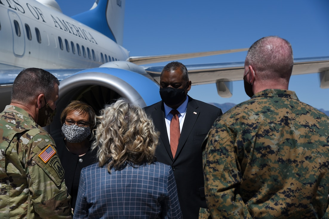 Secretary of Defense and other military personnel talk on the flight line.