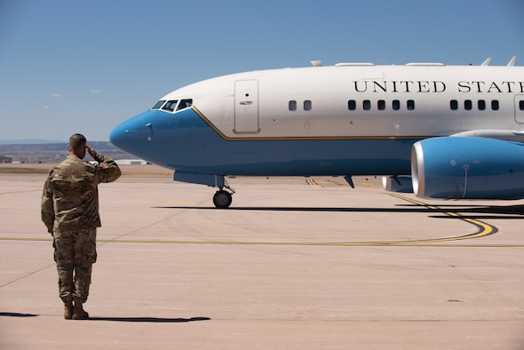 Army. Gen salutes the plane the Secretary of Defense is flying in on.
