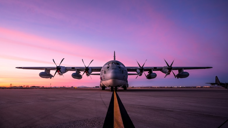 A C-130 sits parked on the flight line while the sunrise happens behind it