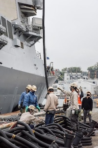 Ship Repair Facility and Japan Regional Maintenance Center's service craft repair shop personnel detach shore power cables from USS Milius (DDG 69) in preparation for sea trials.