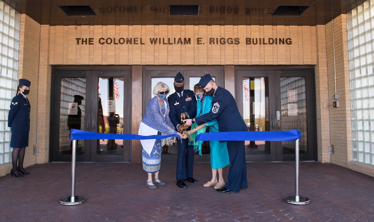 Two women and two uniformed men cut a ribbon in front of a building.