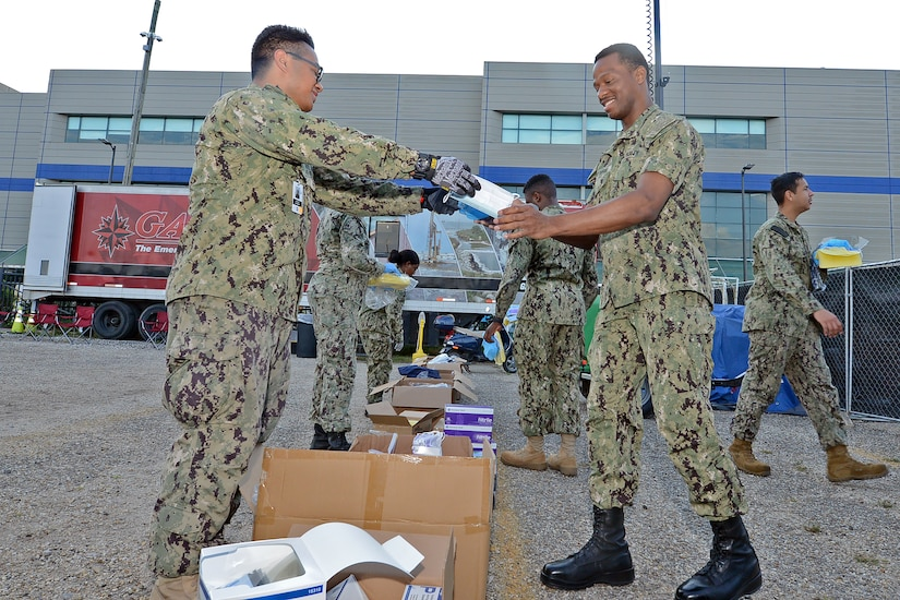 A sailor hands a box to another sailor.