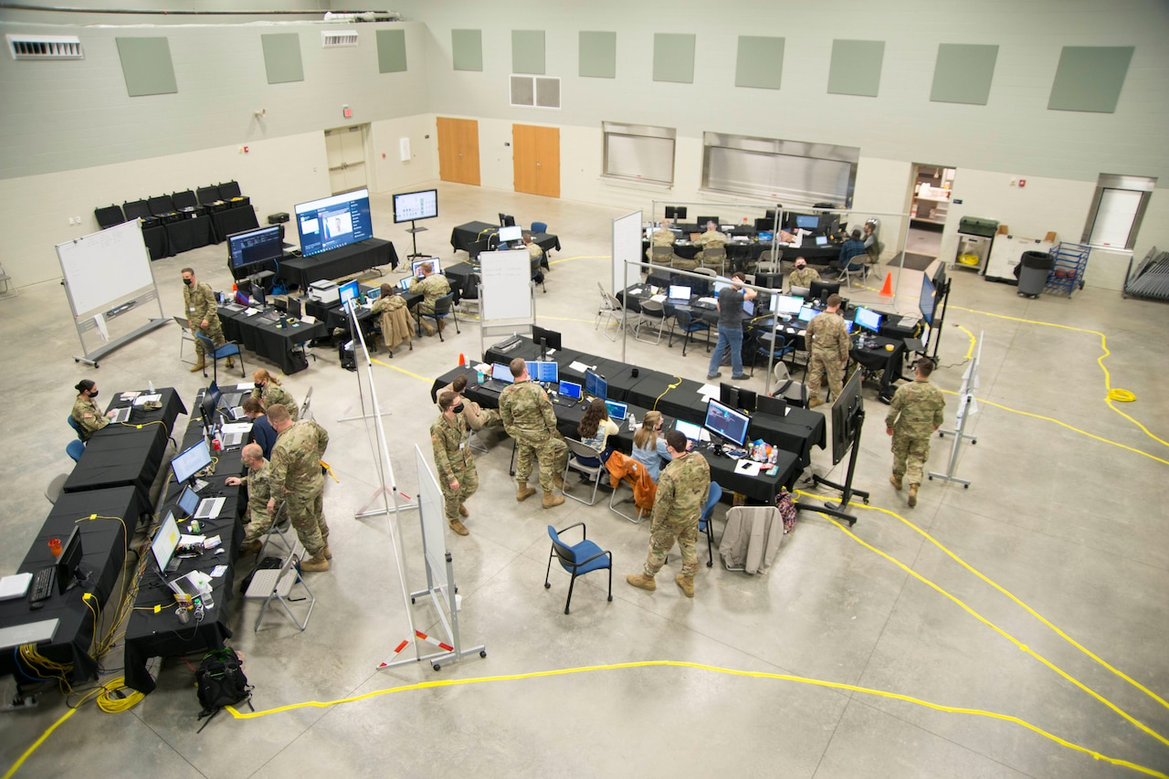Service members work at long tables in a big room.