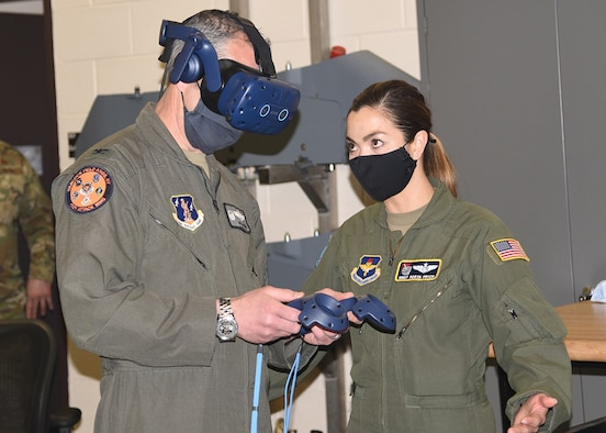 Master Sgt. Robyn Pryor., (right) from Air Education and Training Command, helps Col. William McCrink III, the commander of the 174th Attack Wing, with a demo virtual reality system. The system has two controllers with sensors, headset and a laptop with software that allows the user to explore an aircraft in different digital environments for training purposes. (U.S. Air Force photo by Master Sgt. Barbara Olney)