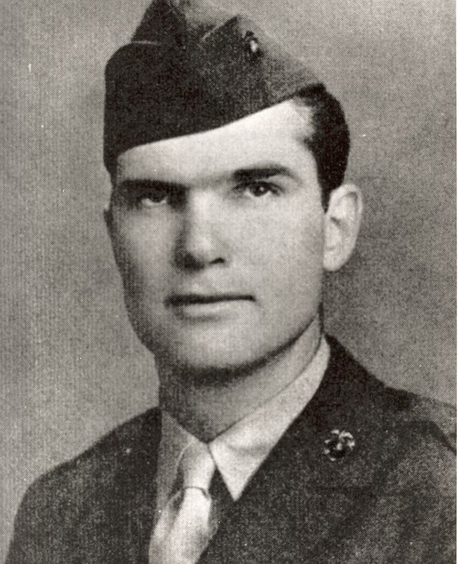 A serious looking man in a cap and uniform looks at the camera.