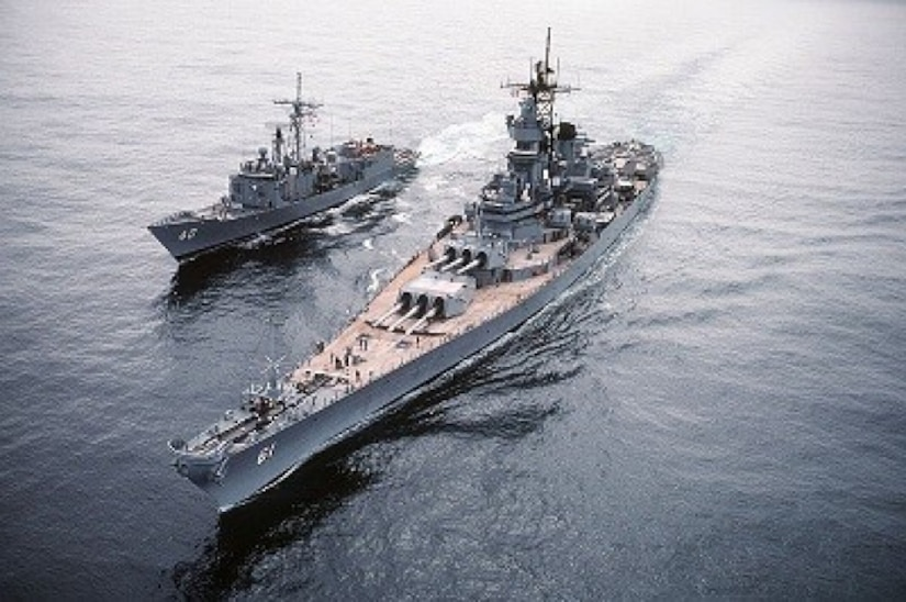 A ship sits in waters left of a much larger refueling ship.