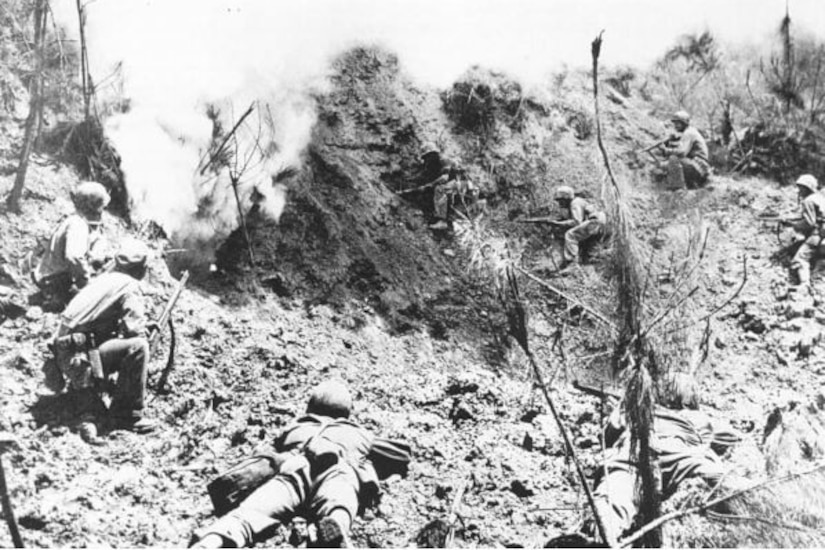 Men with rifles crouch several feet from a hillside cave entrance that has smoke coming out of it.