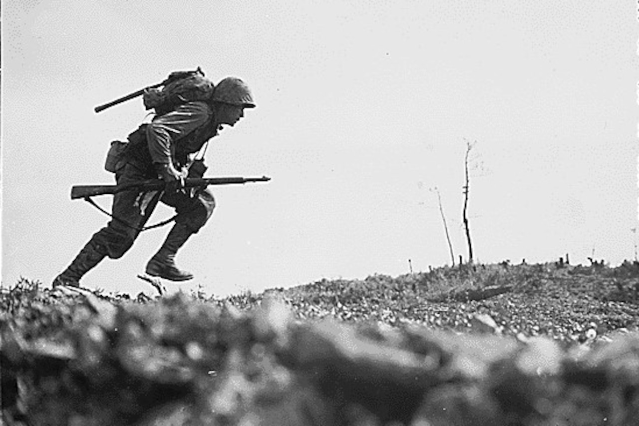 A man with a rifle sprints across a flat surface.