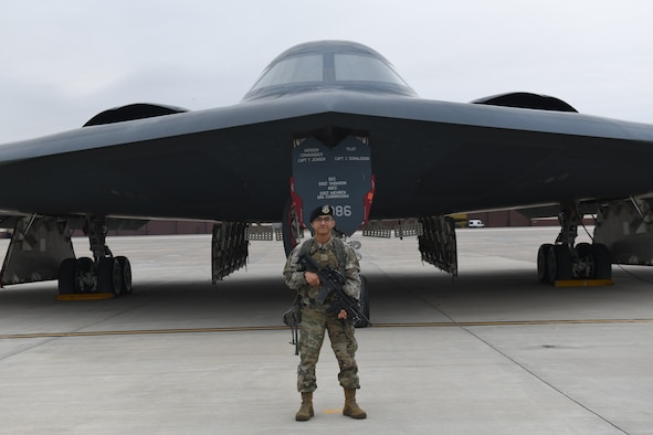 Airman 1st Class Elijah R. Posana, security response team member with the 509th Security Forces Squadron, stands in front of B-2 Spirit at Whiteman Air Force Base, Missouri, Nov. 18, 2020. Members of the 509th SFS protect both personnel and assets supporting the U.S. Air Force Global Strike's stealth bomber fleet. (U.S. Air Force photo by Staff Sgt. Alexandria Lee)